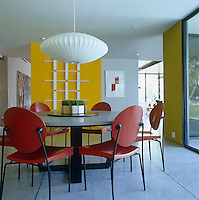 A George Nelson pendant light in the dining room hangs above a round table surrounded by modern chairs