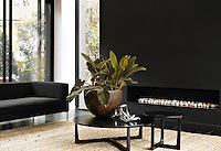Black basalt walls and stone floors are a feature of the minimally furnished living room