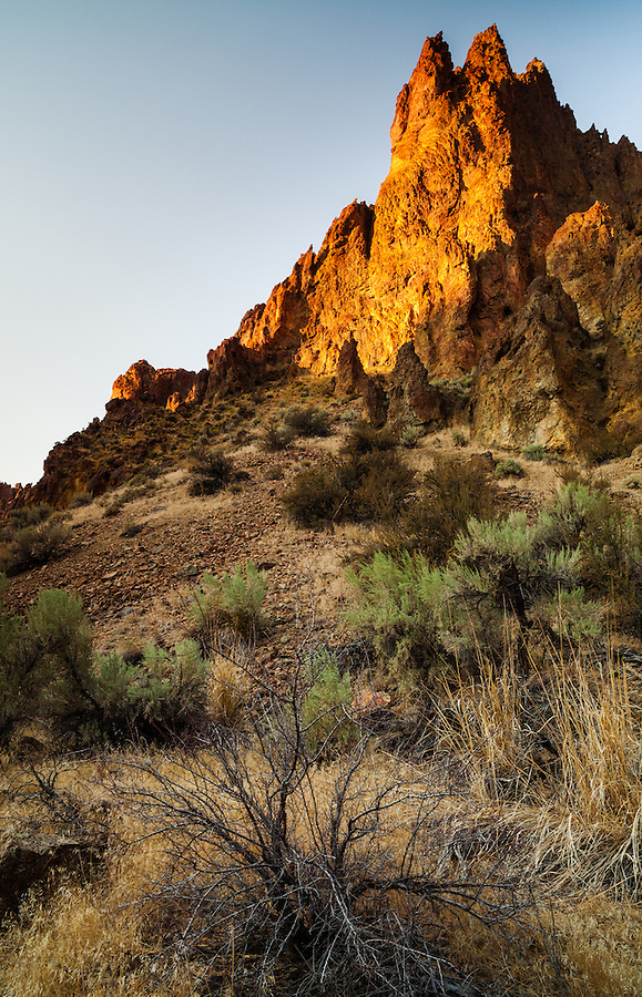 The sharp volcanic tuff spires of Leslie Gulch are lit by the orange-gold light of sunset in Southeast Oregon.