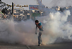 A Palestinian youth runs from tear gas fired by Israeli soldiers during clashes at the Kalandia checkpoint near the West Bank city of Ramallah October 8, 2009. Photo by Mohamar Awad