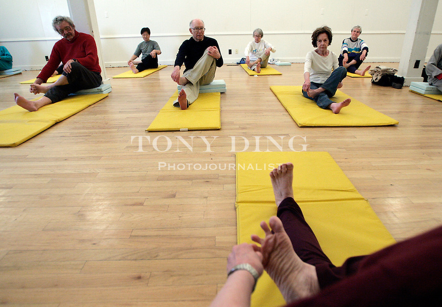 Donna Pointer (feet shown), a yoga instructor of 30 years, leads a group of senior citizens in her weekly class on Tuesday, April 4, 2006 at the Senior Center in Ann Arbor, MI. (AP Photo/Tony Ding)