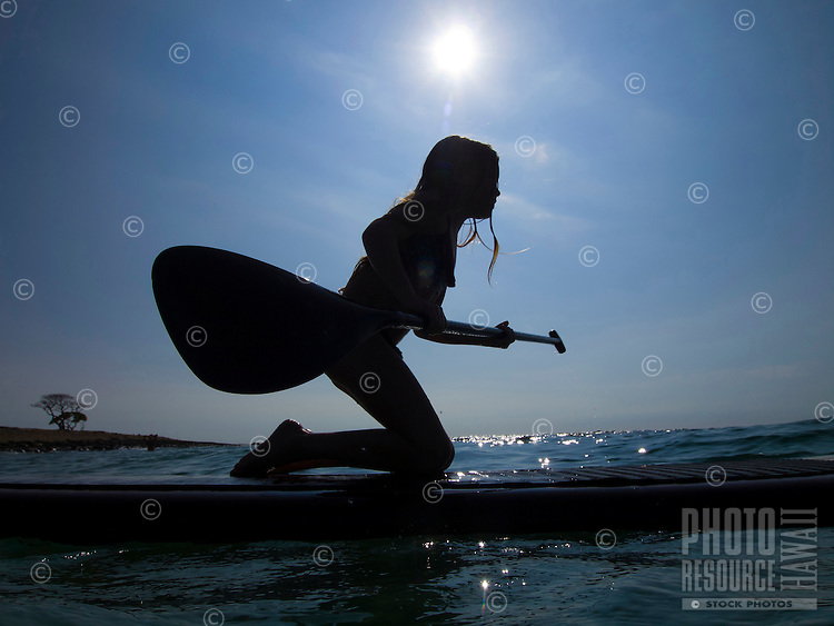 A young girl learns how to standup paddleboard at Mahai'ula Beach (part of Kekaha Kai State Park), Big Island.