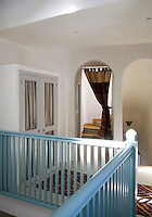 Arched doorways lead off the landing of the Casita, its turquoise balustrade overlooking the living room below