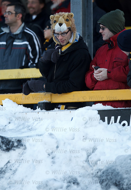 An Alloa fan with warm headgear as he checks out the snow