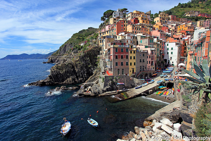 """One of the five villages that are a part of the """"Cinque Terre"""", a rugged portion of coast on the Italian Riviera. Riomaggiore is caught between two steep terraced hills descending in steep cliffs to the sea with its delightfully colored houses built vertically."""