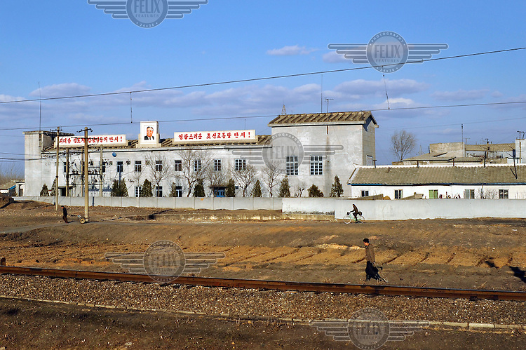 A portrait of Eternal President Kim Il-sung adorns a large rural building, as seen from a train travelling from the Chinese border to Pyongyang.