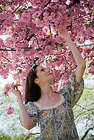 Young woman reaching up towards flowering tree