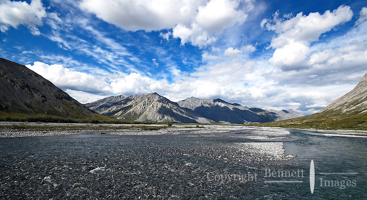 The Marsh Fork of the Canning River flows over a gravel bed, between high mountains and under a startling sky.