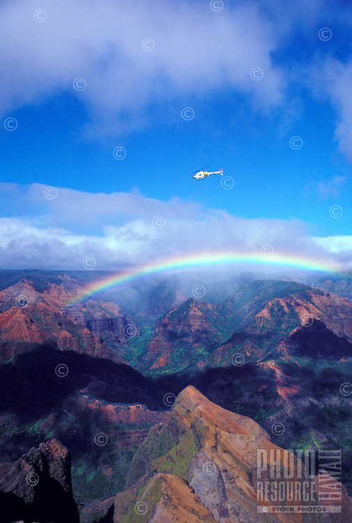Helicopter flying over Waimea Canyon with rainbow, Island of Kauai, Hawaii