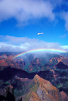 Helicopter flying over Waimea Canyon with rainbow, Island of Kauai, Hawaii