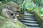 Ubud, Bali, Indonesia; a moss covered stone sculpture in the wall alongside a staircase on the grounds of the Tjampuhan Hotel