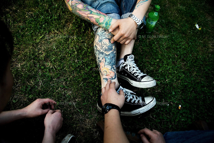 Chinese punk musicians compare tattoos in a park outside of the YuYinTang rock club in Shanghai, China.