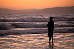 Young man surf fishing in coastal waves at sunset Morro Strand State Beach,, near Cayucos and Morro Bay, California