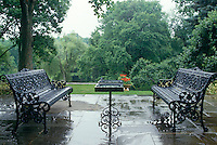 Rain-soaked wrought-iron benches face each other on a stone-flagged terrace overlooking the garden