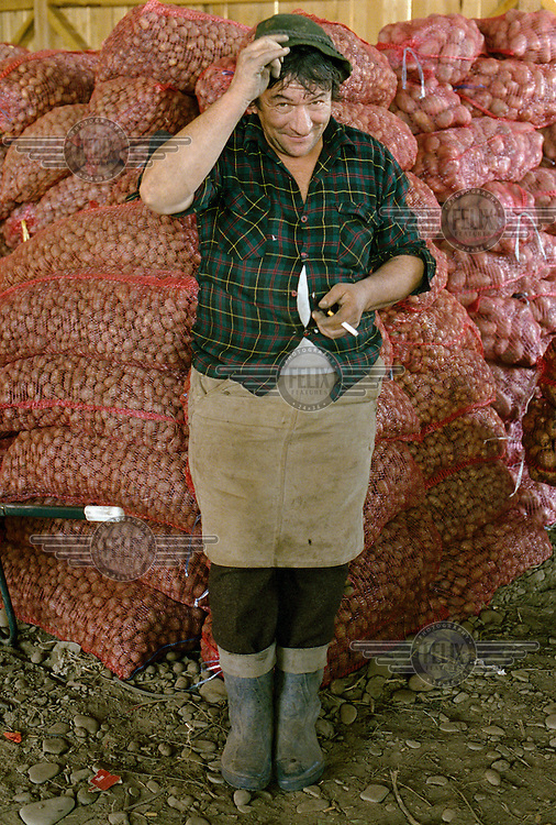 A seasonal worker takes a cigarette break next to sacks of potatoes harvested on a farm..