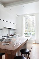 A raised breakfast bar stands at one end of the island of this spacious kitchen