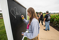 NWA Democrat-Gazette/SPENCER TIREY     Kyler Greenlee places the name of her brother, Billy Jack, on a chalkboards, Sunday, Sept. 9, 2018 in Orchard Park, Bentonville, where those walking in the NWA Out of Darkness Walk could place the names of a person they were walking for. Hundreds of people walked in the 5th annual walk to support the American Foundation for Suicide Prevention. The goal is to reduce the annual suicide rate 20 percent by 2025.