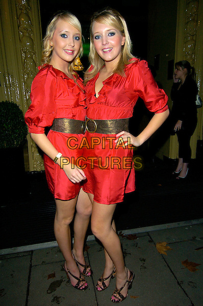 SAM & AMANDA MARCHANT - BIG BROTHER.Leaving the Specsavers Spectacle Wearer Of The Year 2007  Awards, The Waldorf Hilton Hotel, London, England. .October 9th, 2007.full length red dress gold belt hand on hip twins sisters siblings family matching.CAP/CAN.©Can Nguyen/Capital Pictures