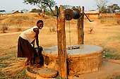 Kapatu, Zambia, Africa. A smiling young girl with a barrel of water from the village well.