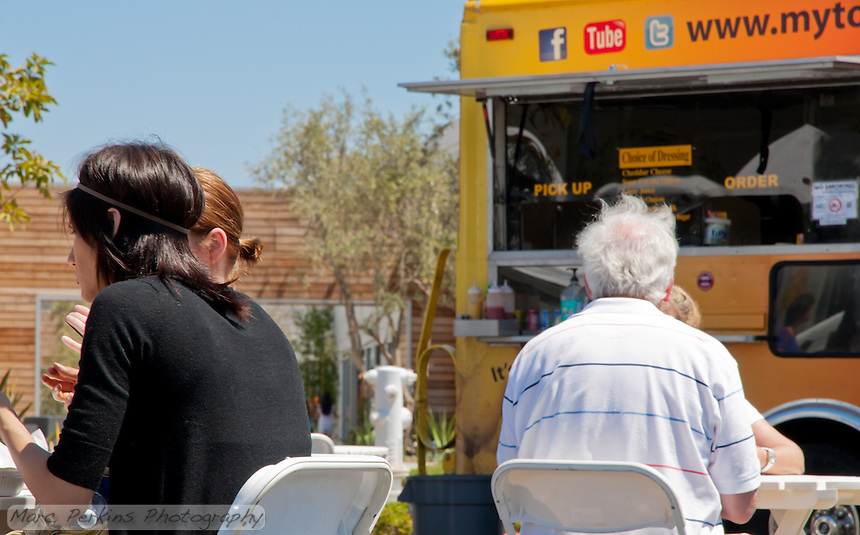 People eat in an area with tables and chairs surrounded by food trucks, farmers market vendors, and SoCo's xeriscaped courtyard.  My Tornado Potato truck is visible.