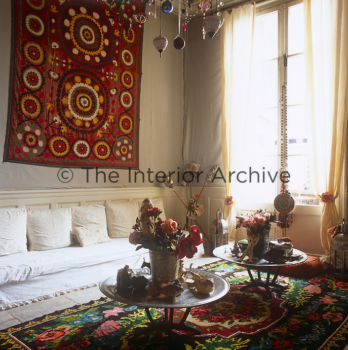 A living room with a grey wall covering and colourful patterned rug. Two low round metal tables are placed in front of a simple sofa. the room has part panelling and sheer curtains at a french window.
