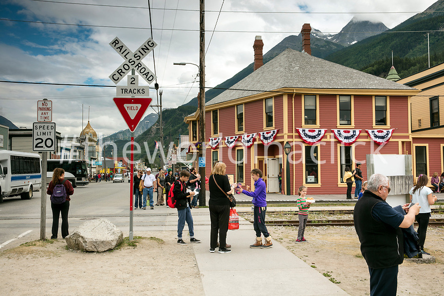 USA Alaska, Sitka, individuals walking the streets of downtown Sitka wait for the train traveling on the White Pass & Yukon Route Railroad to pass