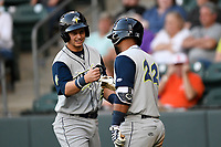 Left fielder Matt Winaker (5) of the Columbia Fireflies is congratulated by Walter Rasquin (22) after scoring a run in a game against the Greenville Drive on Wednesday, April 18, 2018, at Fluor Field at the West End in Greenville, South Carolina. Columbia won 8-4. (Tom Priddy/Four Seam Images)