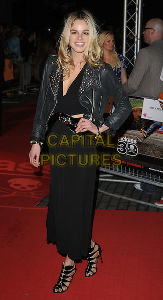 NATASHA GILBERT.attending the UK premiere of 'Jackass 3D' at BFI IMAX, London, England, UK,  November 2nd, 2010..full length black long maxi dress cut out shoes sandals leather studded jacket studs tasha hand on hip .CAP/CAN.©Can Nguyen/Capital Pictures.