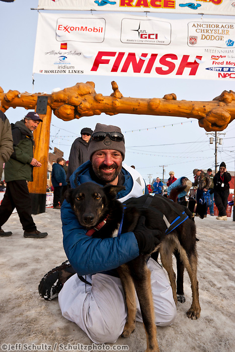 Scott White poses with his lead dog Stinger at the finish line in Nome during the 2010 Iditarod