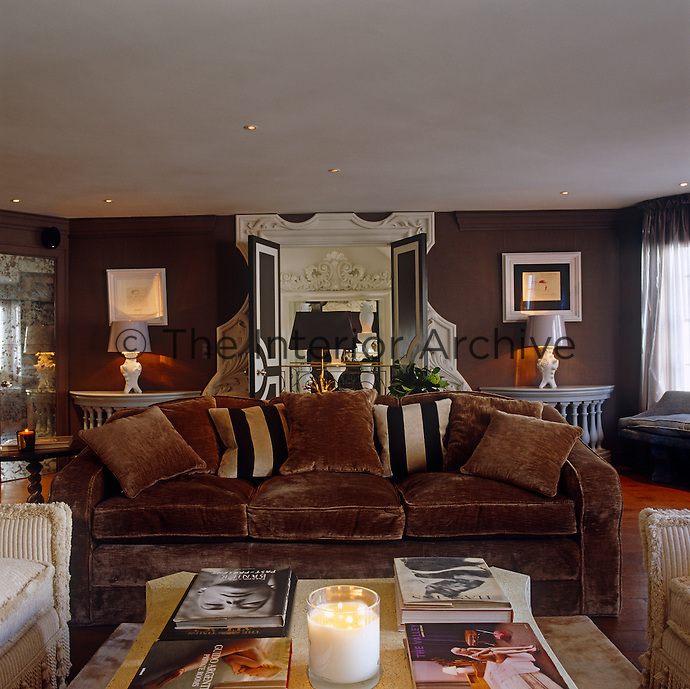 A large brown velvet sofa takes centre stage in this warm  and comfortable drawing room