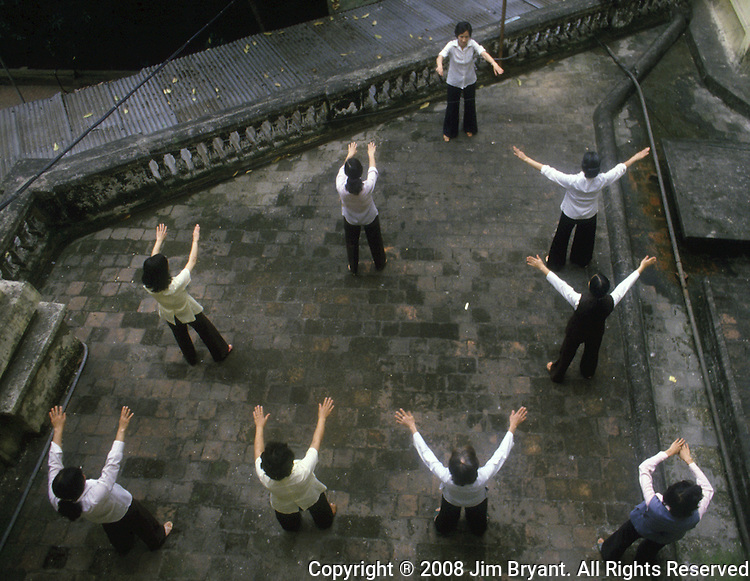 Thang Nhat Hotel workers perform morning exercises on a balcony overlooking the courtyard in Hanoi, North Vietnam.  (Jim Bryant Photo)......