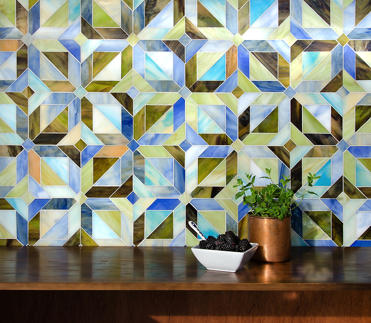 Rubrik, a jewel glass waterjet mosaic shown in Olivine, Aquamarine, Peridot, Blue Onyx, and Chalcedony, is part of the Parquet Line by Sara Baldwin for New Ravenna.
