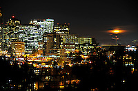 Night skyline of the city of Bellevue, Washington with a moon rising over a crane and the distant Cascade Mountains. Washington State.