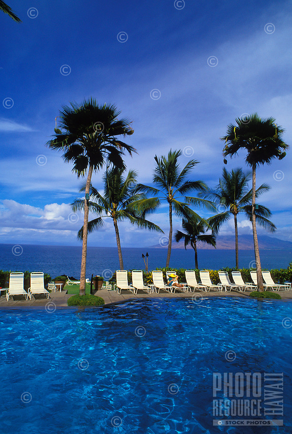 A tourist enjoys the sun and relaxes at the Wailea Marriott (the old Intercontinental Hotel) pool, with tall palms overhead and the West Maui Mountains in the background.