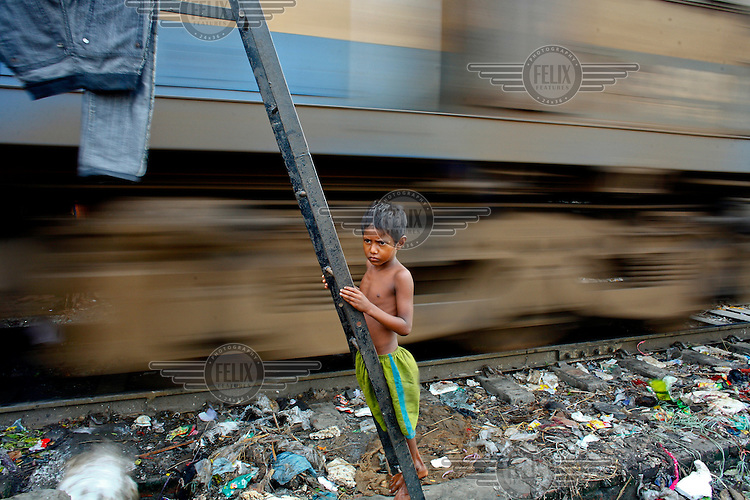 A young boy stands on a ladder that forms part of the railway infrastructure as a train passes by on its route through one of the city's slum districts. It is thought that more than six million people live in slums in Dhaka.