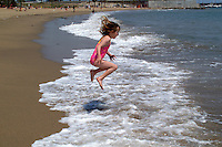 Young girl jumping over a wave at the beach in Barcelona, Spain.