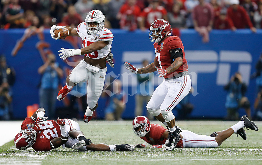 Ohio State Buckeyes running back Ezekiel Elliott (15) leaps over Alabama Crimson Tide defensive back Landon Collins (26) on his way to a 54-yard run in the first quarter of the Allstate Sugar Bowl and College Football Playoff Semifinal at Mercedes-Benz Superdome in New Orleans, Thursday night, January 1, 2015. (The Columbus Dispatch / Eamon Queeney)