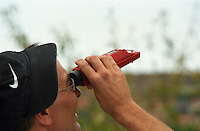 A person looking through a refractometer, a device to measure sugar contents in grape juice in order to evaluate the maturity of the grapes at harvest time, Languedoc-Roussillon, France