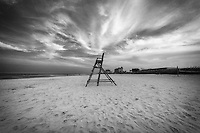 Iconic lifeguard chair on Jax beach with an ominous sky rendered monochrome.