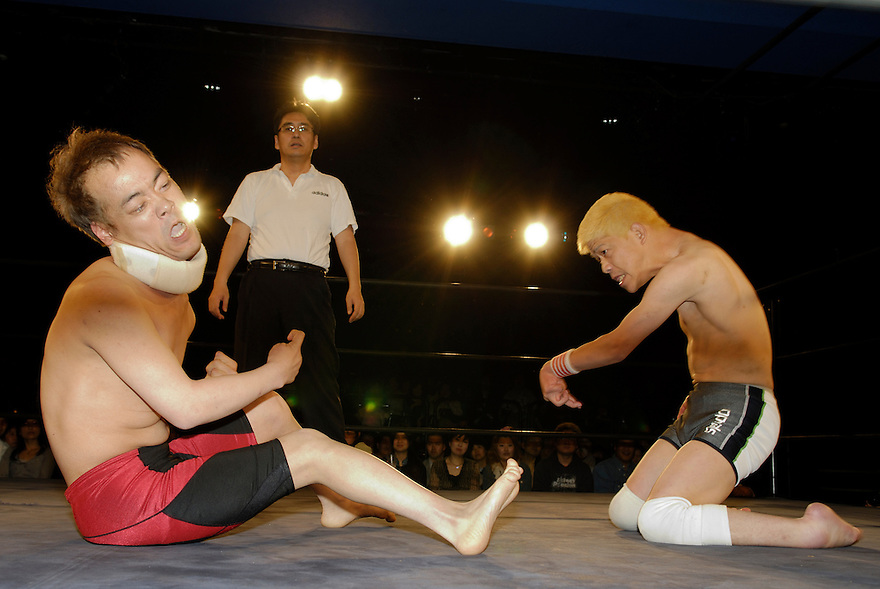 """Yokkoisho"" fights with Yasuhiro Kayahara, AKA ""No Sympathy"". Both wrestlers suffer from cerebral palsy. Referee Shinsuke Funabashi watches on."