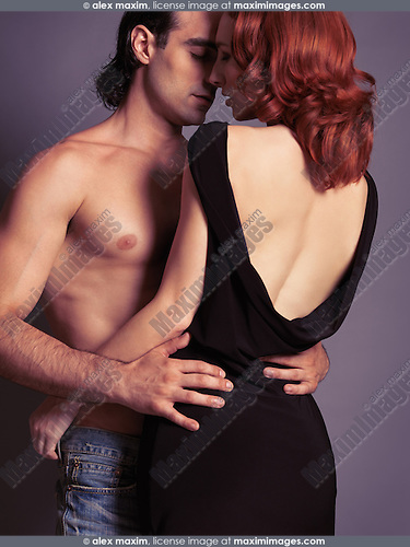 Sensual portrait of a young sexy couple. Man with bare torso embracing a woman in dress with open low back. Isolated on gray background.