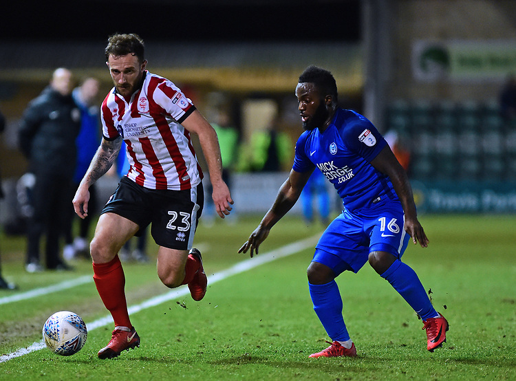 Lincoln City's Neal Eardley vies for possession with  Peterborough United's Junior Morias<br /> <br /> Photographer Andrew Vaughan/CameraSport<br /> <br /> The EFL Checkatrade Trophy Fourth Round - Lincoln City v Peterborough United - Tuesday 23rd January 2018 - Sincil Bank - Lincoln<br />  <br /> World Copyright &copy; 2018 CameraSport. All rights reserved. 43 Linden Ave. Countesthorpe. Leicester. England. LE8 5PG - Tel: +44 (0) 116 277 4147 - admin@camerasport.com - www.camerasport.com