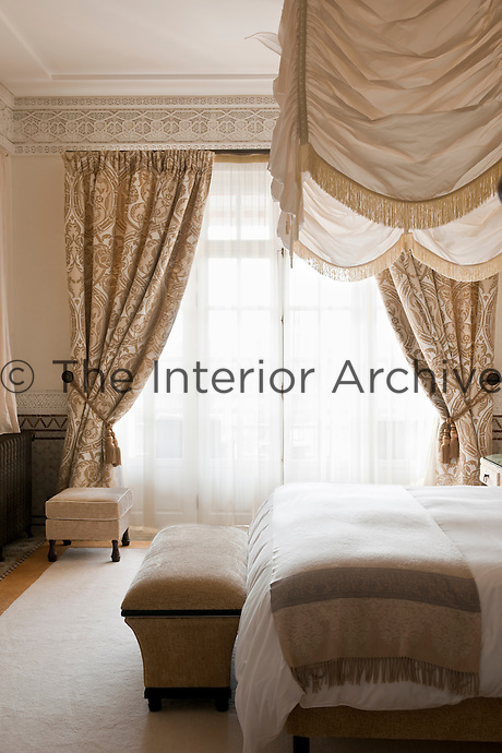 A bright bedroom with elegant bed hangings and patterned beige curtains