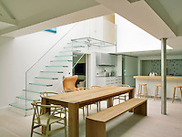 A glass staircase and a long wooden dining table perfectly match the contemporary atmosphere in the kitchen dining area of this converted manor house