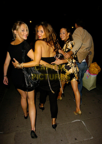 JODIE ALBERT, ALI BASTIAN & ROXANNE McKEE.Roxanne McKee's Birthday Party at Aura nightclub, London, UK..August 10th, 2006.Ref: CAN.full length black dress bag purse looking over shoulder.www.capitalpictures.com.sales@capitalpictures.com.©Can Nguyen/Capital Pictures