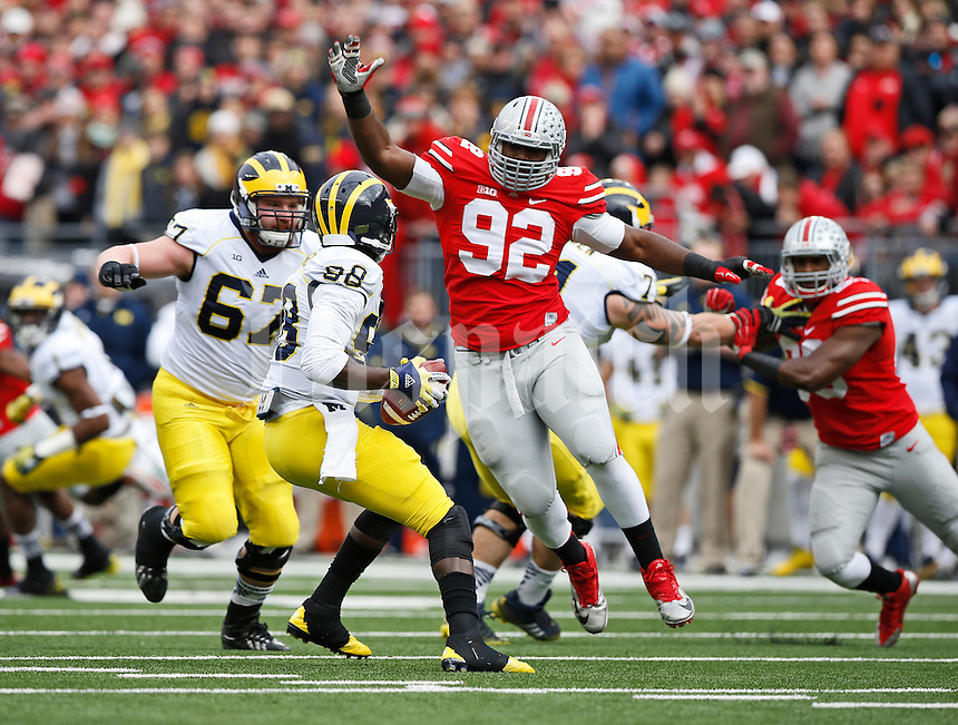 Ohio State Buckeyes defensive lineman Adolphus Washington (92) leaps before sacking Michigan Wolverines quarterback Devin Gardner (98) during the 1st quarter of the NCAA football game at Ohio Stadium on Nov. 29, 2014. (Adam Cairns / The Columbus Dispatch)