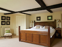 A large traditional wooden bed furnishes one of the bedrooms in this converted manor house