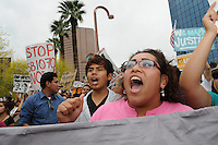 Phoenix, Arizona. April 25, 2012 - Leticia Ramirez (pink blouse), among other demonstrators, chant at the end of the march's route in front of the ICE building on Central Avenue. Ramirez is an undocumented mother of three children who are U.S. citizens. About 500 people protested the controversial law on the same day U.S. Supreme Court justices heard legal arguments on the Arizona vs. United States case. At the end of the march, six activists blocked Central Avenue by sitting in the middle of the street. They all were arrested by the Phoenix Police Department and taken to the Fourth Avenue County Jail. Photo by Eduardo Barraza © 2012