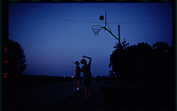 Two boys play basketball at night on a sectional of pavement that was part of the National Road in a rural part of Illinois.