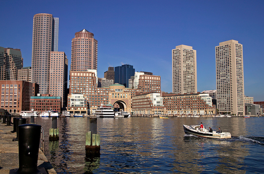 People commute in small water taxi boat in Boston Harbor with city skyline view from Federal Courthouse waterfront park, Boston, M